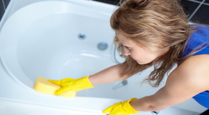 Young Woman Cleaning A Bath With Sponge